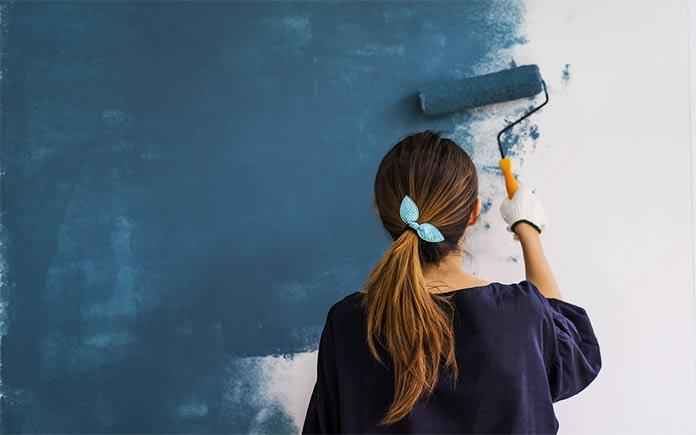 Mujer joven pintando una pared azul