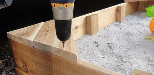 Usando tornillos para sujetar el asiento de la caja de arena.