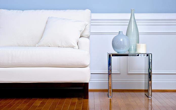 Revestimiento de madera instalado sobre una pared azul pálido en una sala de estar.