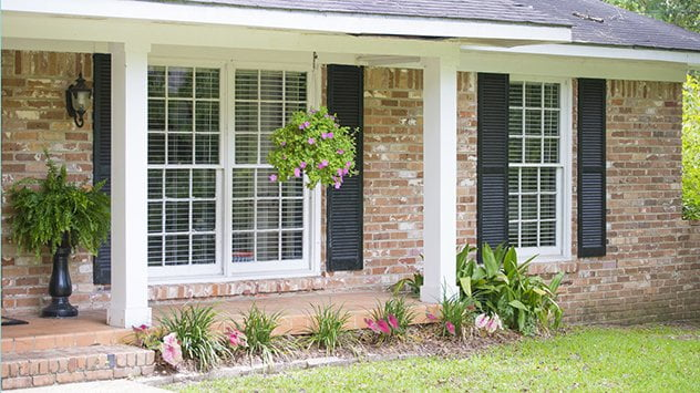 Frente de la casa con parterre y plantas colgantes.