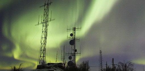 Aurora boreal sobre torres de comunicación